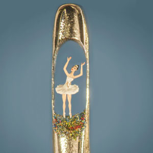 Close-up view of a miniature ballerina created by artist Willard Wigan in the eye of a needle