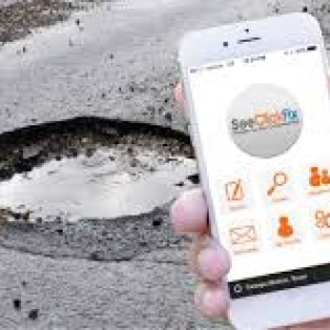 a pothole and someone taking a photo of it