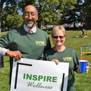 Two people wearing UVM Employee Wellness shirts, holding inspire wellness sign.