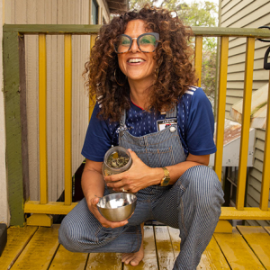 jackie sumell  on a porch with goodies in a jar