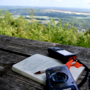 a notebook, camera, and GPS lie on a picnic table with a beautiful vista beyond