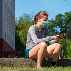 Student wearing a mask looking at her mobile phone
