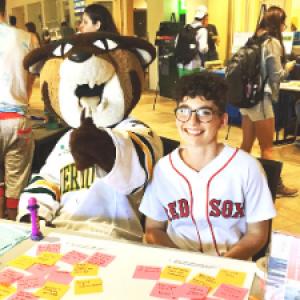UVM's Rally Cat mascot and HESA practicum student tabling at an event