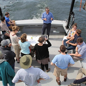 Students listen to an instructor lecture aboard a boat