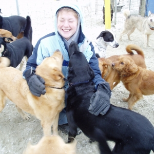 Student hugging pack of dogs