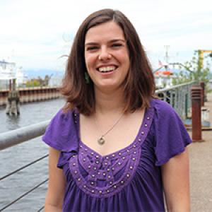 Caroline Blake stands on dock by Rubenstein Lab on Lake Champlain