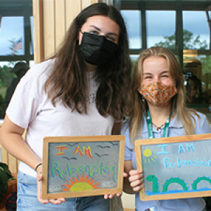 Two students wearing masks and holding I Am Rubenstein chalk boards