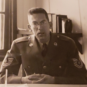 Charette in uniform sitting at a desk