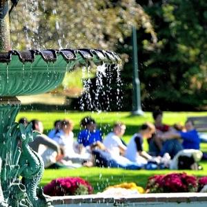Water fountain on university green, students sitting around it.