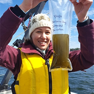 Student holds up water sample bag on boat on lake