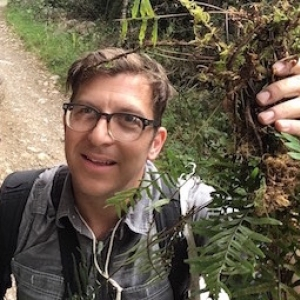 Michael in the field, holding up a fern