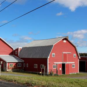 image description: large red barn under a blue sky