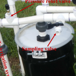 image description: white pipes and a black drum  labeled with red indicating direction of the water to be filtered and how this item works