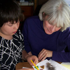A teacher assisting a student with their school work.