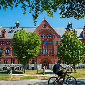 Cyclist in front of Wiliams Hall in spring