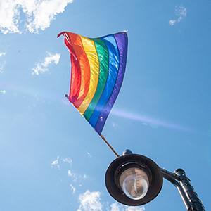 Rainbow Pride flag flies over lamp post against blue sky