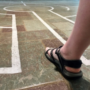 A person's foot walking into the labyrinth pattern