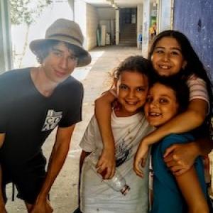 student with children in Peru