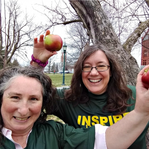 Two people standing by a tree, holding apples.