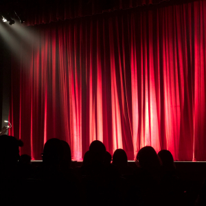 A stage with red curtain drawn