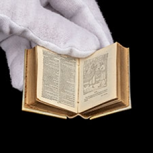Gloved hand holding a miniature Bible