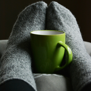 Cozy mug of tea resting between two stockinged feet