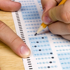 hands filling in a scantron test sheet