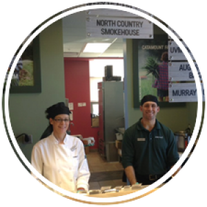 two staff members waiting to serve students at the deli counter