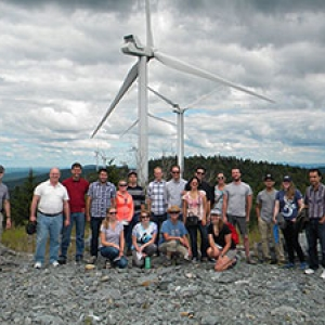 Students pose in front of a windmill farm