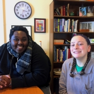 Picture of two students around an office table.