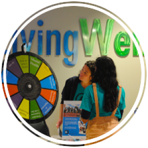 students at a table in front of living well getting ready to spin a wheel