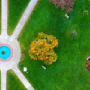 Aerial view of water fountain, lush green grass and sidewalks cutting through.