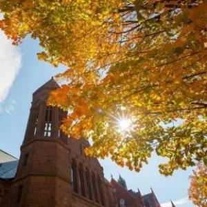 Redstone building with autumn trees.  Sun shining through orange leaves.