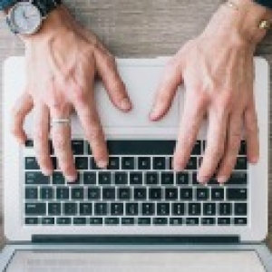 Hands typing on a computer keyboard.