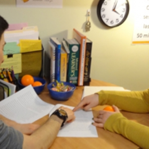 Writing Center tutor reviews a written draft with student.