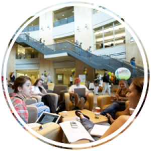 numerous students lounging and discussing on the ground floor of the atrium