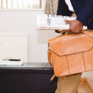 Person standing in an office holding a brown satchel and newspaper.