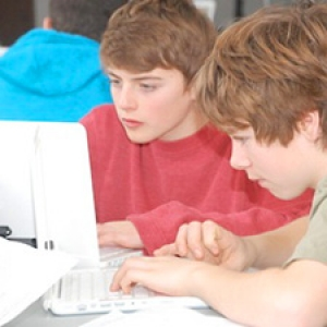 Two students look at the laptop screen
