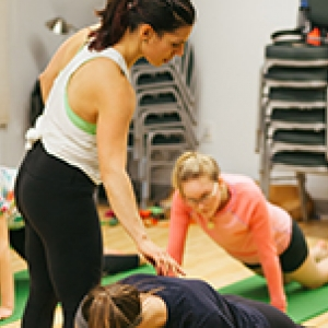 Fitness instructor Suzy Shulman helps a student do a plank