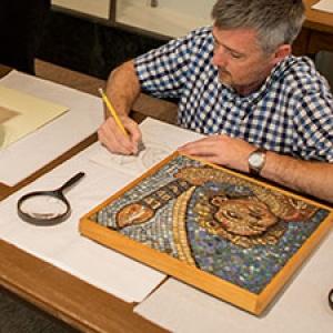 Teacher examining an artifact in a workshop