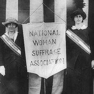 "Old photo with women holding a banner reading ""National Woman Suffrage Association"""