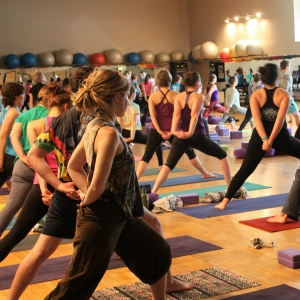Many people participating in yoga at patrick gym.