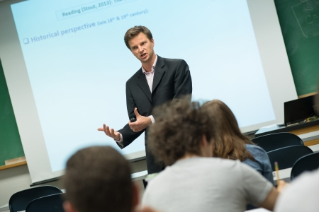 Professor in dark grey suit, leading a lecture in front of a presentation board.
