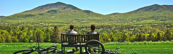 Two people on a bench near bike trail with mountain view