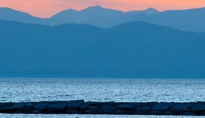 The sun sets over Lake Champlain and behind the Adirondacks