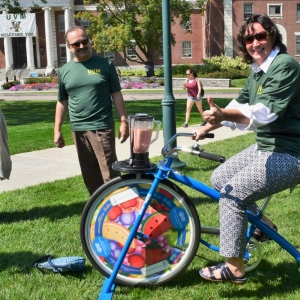 Woman riding smoothie bicycle, wearing green employee wellness shirt.