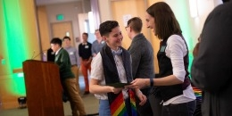 Person shaking hands with a student at rainbow graduation.