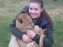 student holding lion cub