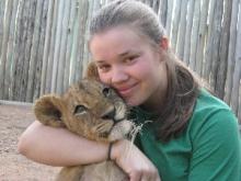 Student hugging lion cub