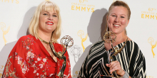 Two women holding Emmy Awards, Marie Schley '94 on the left wearing a bright red floral dress and blonde shoulder length hair with bangs.